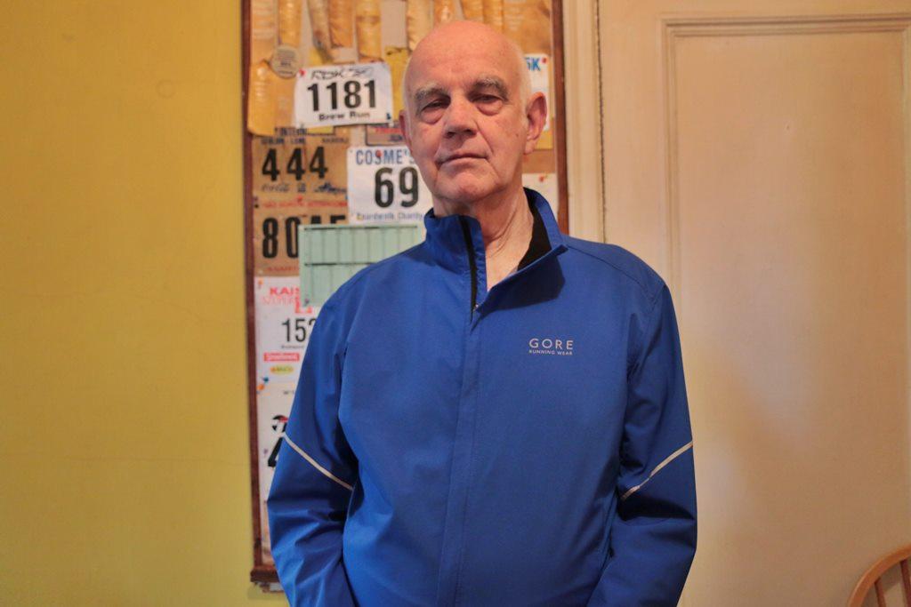 Bill Staab pose devant un tableau ou sont épinglés certains dossards remontant aux années 70