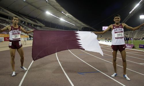Qatar's Mohamad Algarni and Hamza Driouch celebrate during the Men's 1500m final at the 2011 Arab Games in Doha
